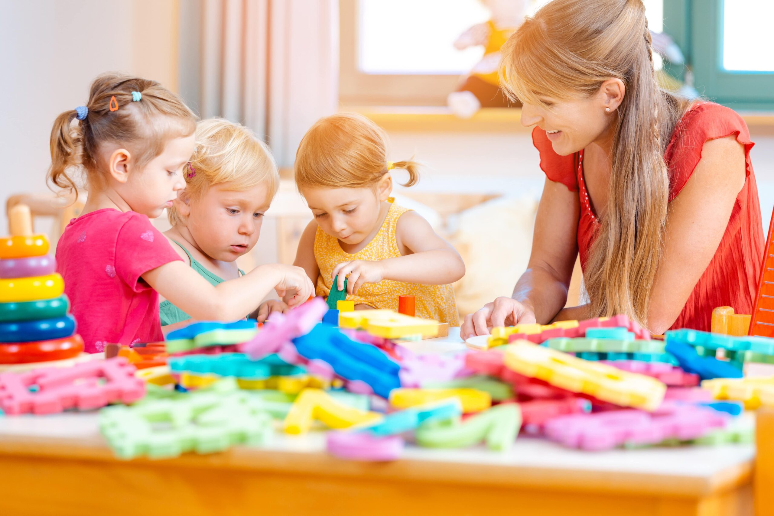 3 kids and 1 woman playing early childhood development